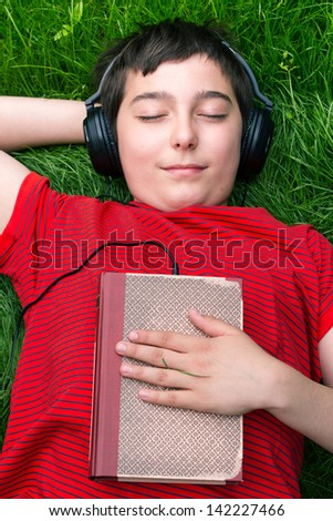 Boy is lying on a grass and he is listening audio book
