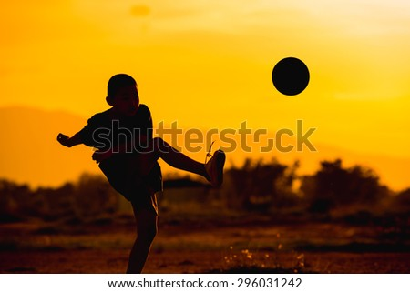 boy is playing football in the sunshine day. - stock photo