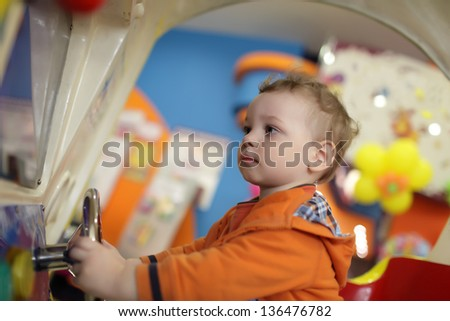 Boy is playing with amusement machine at indoor playground - stock photo