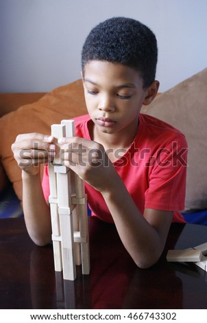 Boy is playing with wooden blocks.