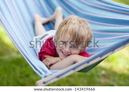 Boy is relaxing in a hammock during summer in the garden - stock photo