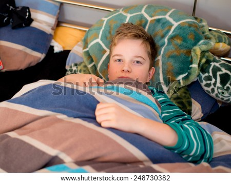boy is resting in the bed and looking in to the camera - stock photo