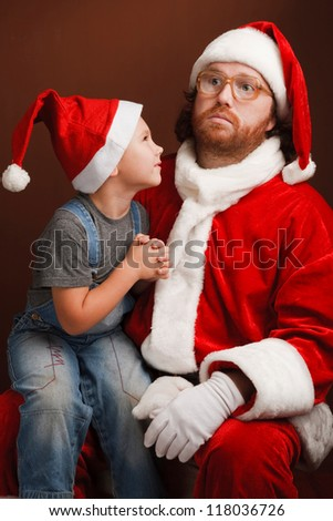 Boy is  sitting on Santas knee and asking about his  present.  Man,dressed in Santa costume looks tired and unhappy