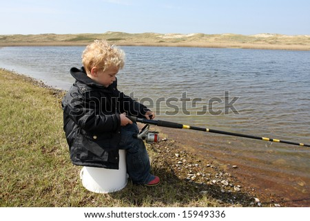 Boy is trying to catch some fish - stock photo