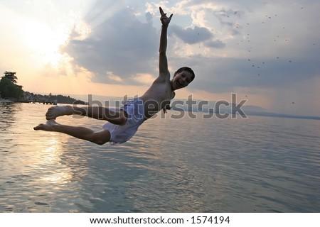 Boy joyfully jumping in the lake at sunset - stock photo
