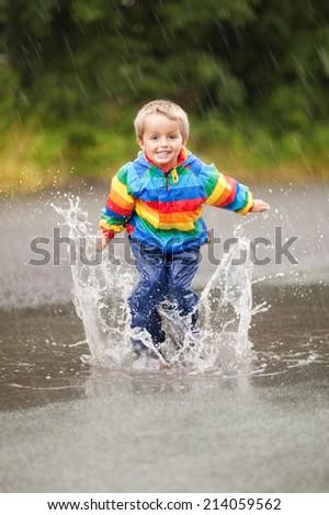 Boy jumping and splashing in rain puddle - stock photo