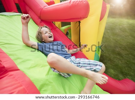 Boy jumping down the slide on an inflatable bouncy castle - stock photo