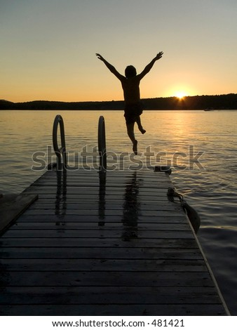 Boy jumping in a lake during sunset - stock photo