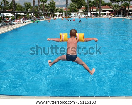 boy jumping in swimming pool - stock photo