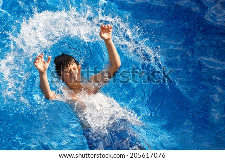 Boy jumping in the home garden swimming pool with clear water