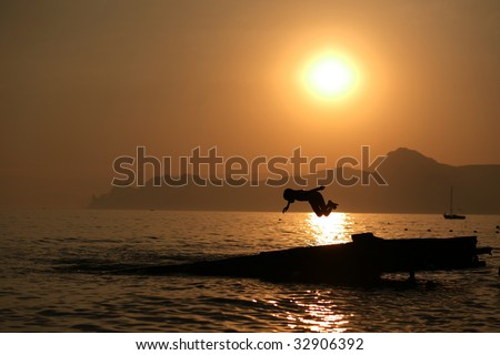 boy jumping in water with sunset at background