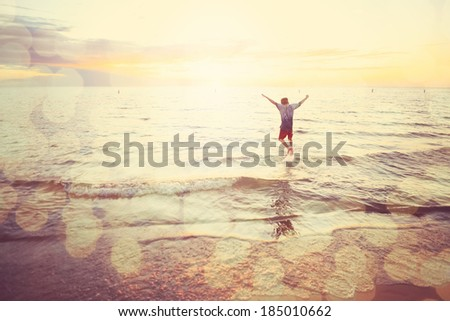 Boy jumping in waves on the beach at sunset - stock photo