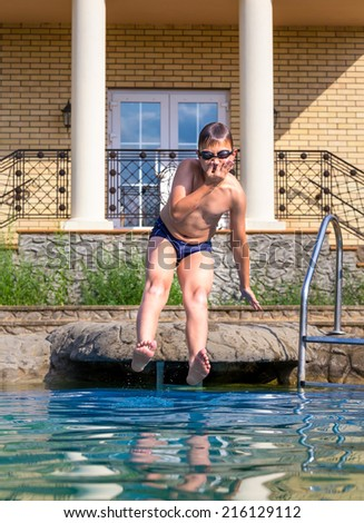 Boy jumping into a swimming pool on a sunny day - stock photo