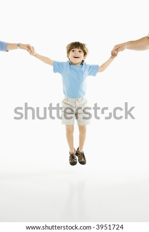 Boy jumping into air holding hands with parents against white background. - stock photo