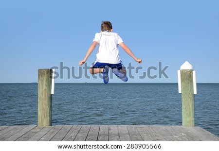 boy jumping into the air off dock into water - stock photo