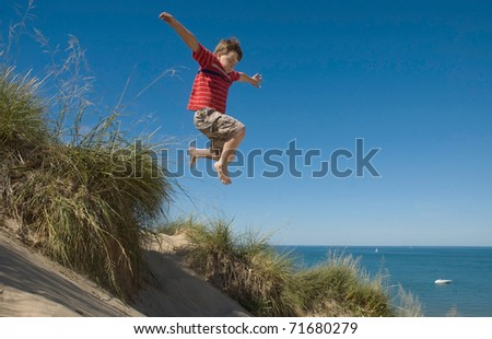 Boy jumping off dune - stock photo
