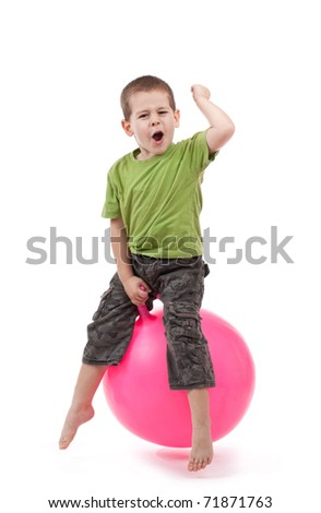 Boy jumping on a large ball - stock photo
