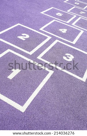 Boy jumping on numbers playground floor - stock photo