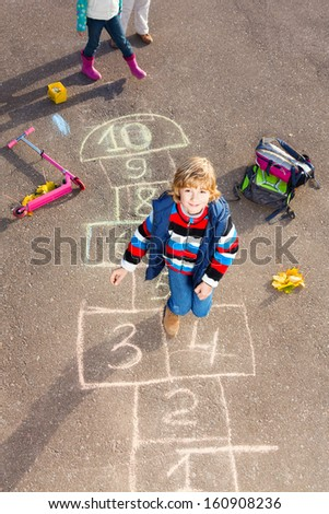Boy jumping on the hopscotch game drawn on the asphalt looking up