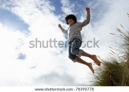 Boy jumping over dune - stock photo