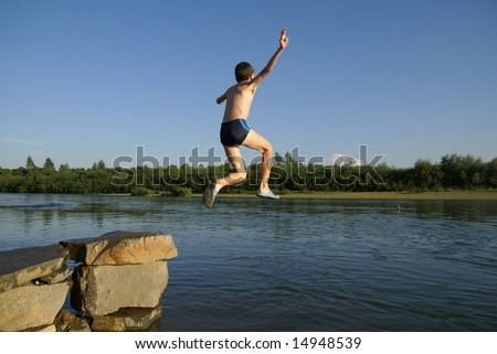 Boy jumps in water from a stone