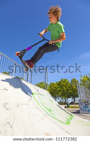 boy jumps with his scooter at the skate park - stock photo