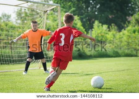 boy kicking a ball at goal - stock photo