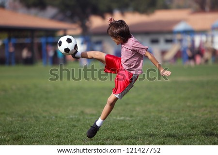 Boy kicking soccer in the park - Authentic action with soccer ball - copy space - landscape format - stock photo