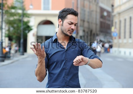 boy late, busy life, looking angry at his watch - stock photo