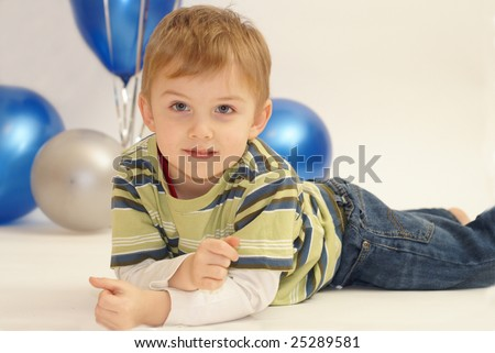 boy laying in front of balloons - stock photo