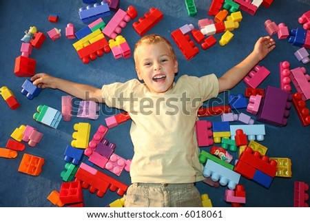 boy laying on floor in playroom - stock photo