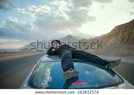 Boy laying on top of car - stock photo