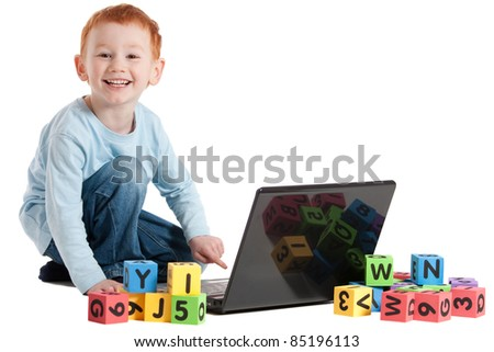 Boy learning reading with notebook computer and kids blocks. Isolated on white. - stock photo