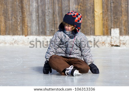 Boy learning to ice skate at an outdoor skating rink in winter.