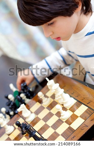 boy learning to play chess - stock photo