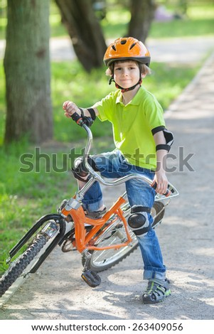 Boy learning to ride a bicycle at the city park  - stock photo