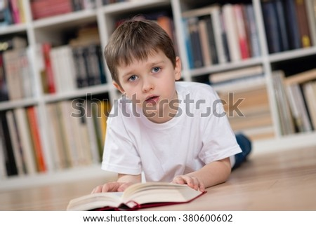 Boy lies on his stomach and reading a book in the library. Dressed in a white t shirt and blue jeans. Looking at camera. - stock photo