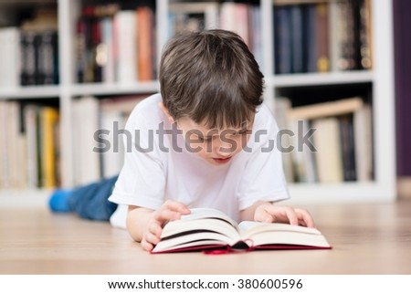 Boy lies on his stomach and reading a book in the library. Dressed in a white t shirt and blue jeans