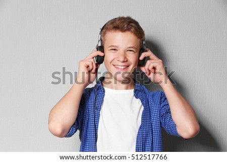 Boy listening music on light background