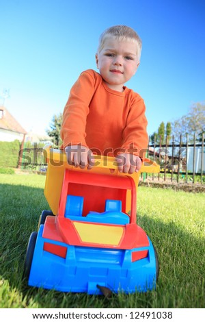 boy little children child play playground  green garden color  car truck toy  life outdoor spring - stock photo