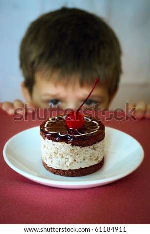 Boy longing to eat sweet cake - stock photo