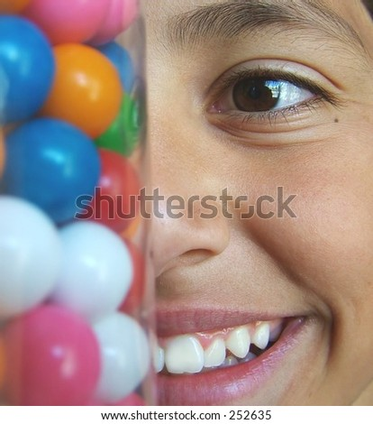 Boy looking at candy jar, grinning - stock photo