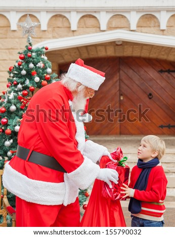 Boy looking at Santa Claus while taking gift from him against house - stock photo