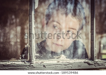 Boy looking out a window - stock photo