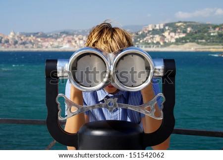 Boy looking through a telescope - stock photo