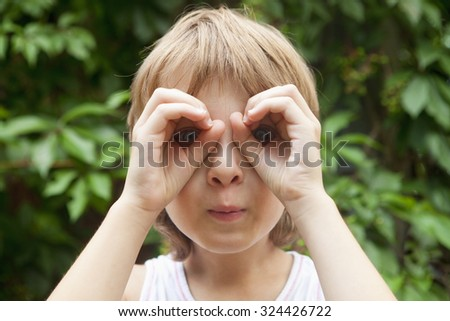 Boy Looking Through Fingers as Binoculars Outdoors