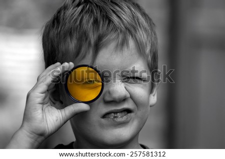 Boy looking through yellow filter. Boy screwing up one eye and viewing the scene through a circular yellow filter.
