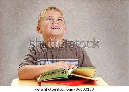 Boy Looking Up at Teacher From School Desk