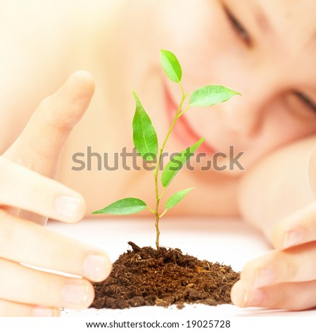 boy looks at a young plant... - stock photo