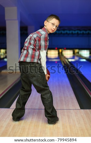 Boy looks back and qualify to throw  ball for bowling - stock photo